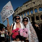 """A couple dressed as brides holds a placard reading """"Just married"""". Photo: Filippo Monteforte/AFP"""