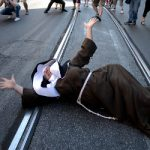 A demonstrator dressed as a nun shouts as she lies on the ground. Photo: Filippo Monteforte/AFP