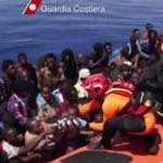 """AUGUST – The number of migrants arriving on Italian shores by boat more than doubled over the summer months, but deputy prime minister, Angelino Alfano, said the influx was """"not an unmanageable emergency"""". In August, officials rescued 300 migrants, including a newborn, from overcrowded boats near Sicily, and accepted 84 migrants whom Malta had refused to admit.Photo: The Italian coast guard help migrants off their vessels. Photo: HO/Guardia Costiera/AFP"""