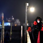 A costumed reveller poses in front of gondolas at St Mark's square (Piazza San Marco) during the Venice Carnival on January 30th, 2016 in Venice.Photo: AFP