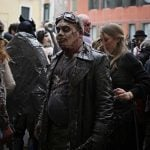 People dressed as zombies wander the streets before the opening ceremony.Photo: Marco Bertorello/AFP