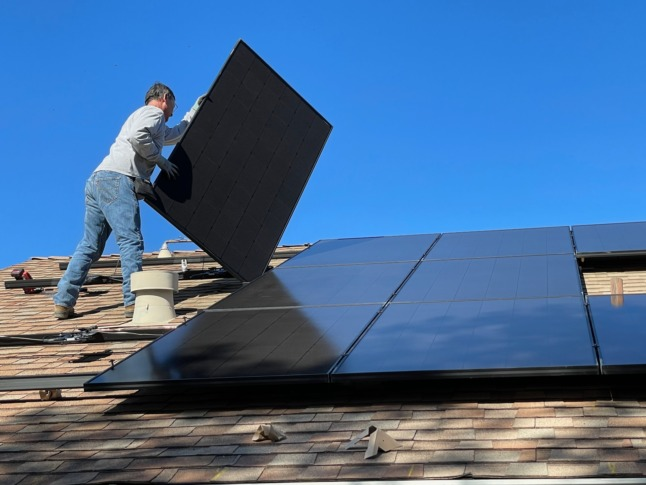 A worker installs solar panels on a roof.