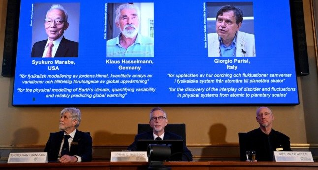 A screen shows the co-winners of the 2021 Nobel Prize in Physics, (L-R) Syukuro Manabe, Klaus Hasselmann and Giorgio Parisi, at the Royal Swedish Academy of Sciences in Stockholm.