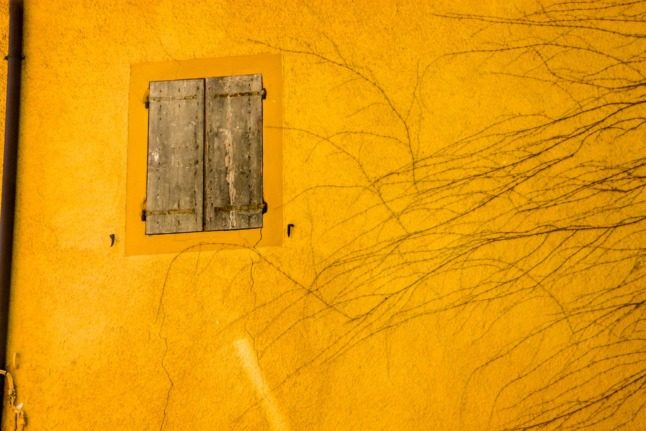 A wooden shutter on a yellow house in Italy.