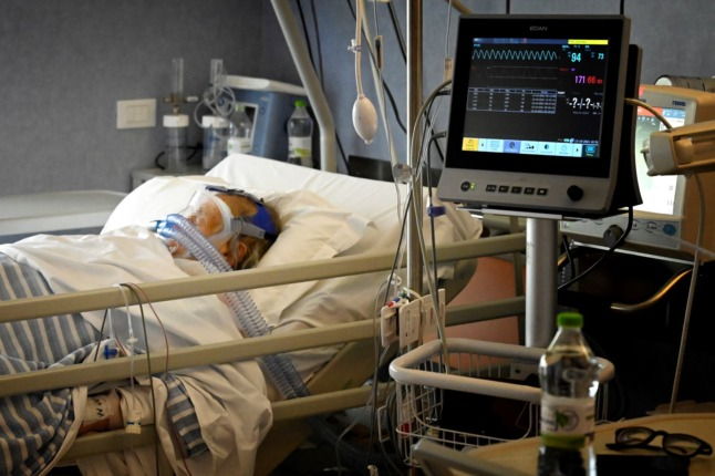 A Covid patient breathes oxygen through a mask at the sub-intensive care unit of the Casalpalocco hospital, south of Rome, on October 13, 2021.