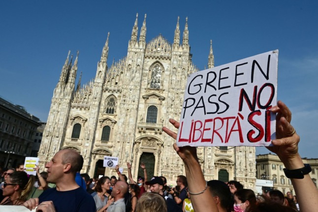 """Protesters take part in a demonstration against the green pass at Piazza Duomo in Milan on July 24, 2021. The placard reads """"Green Pass No, Freedom Yes""""."""