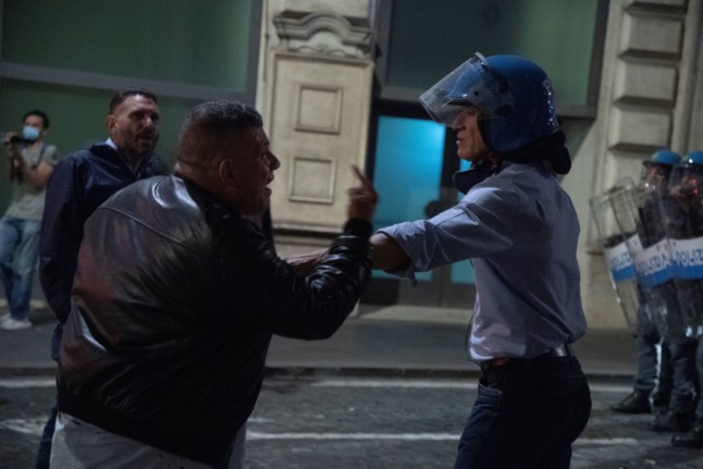 Forza Nuova Rome leader Giuliano Castellino gives a thumb to a riot policeman during clashes in central Rome on October 9, 2021.